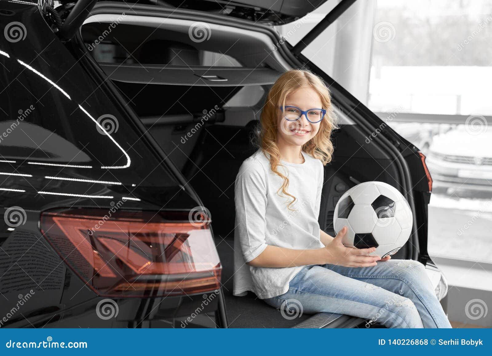 Charma flickan som sitter i bilstam av återförsäljarevisningslokalen