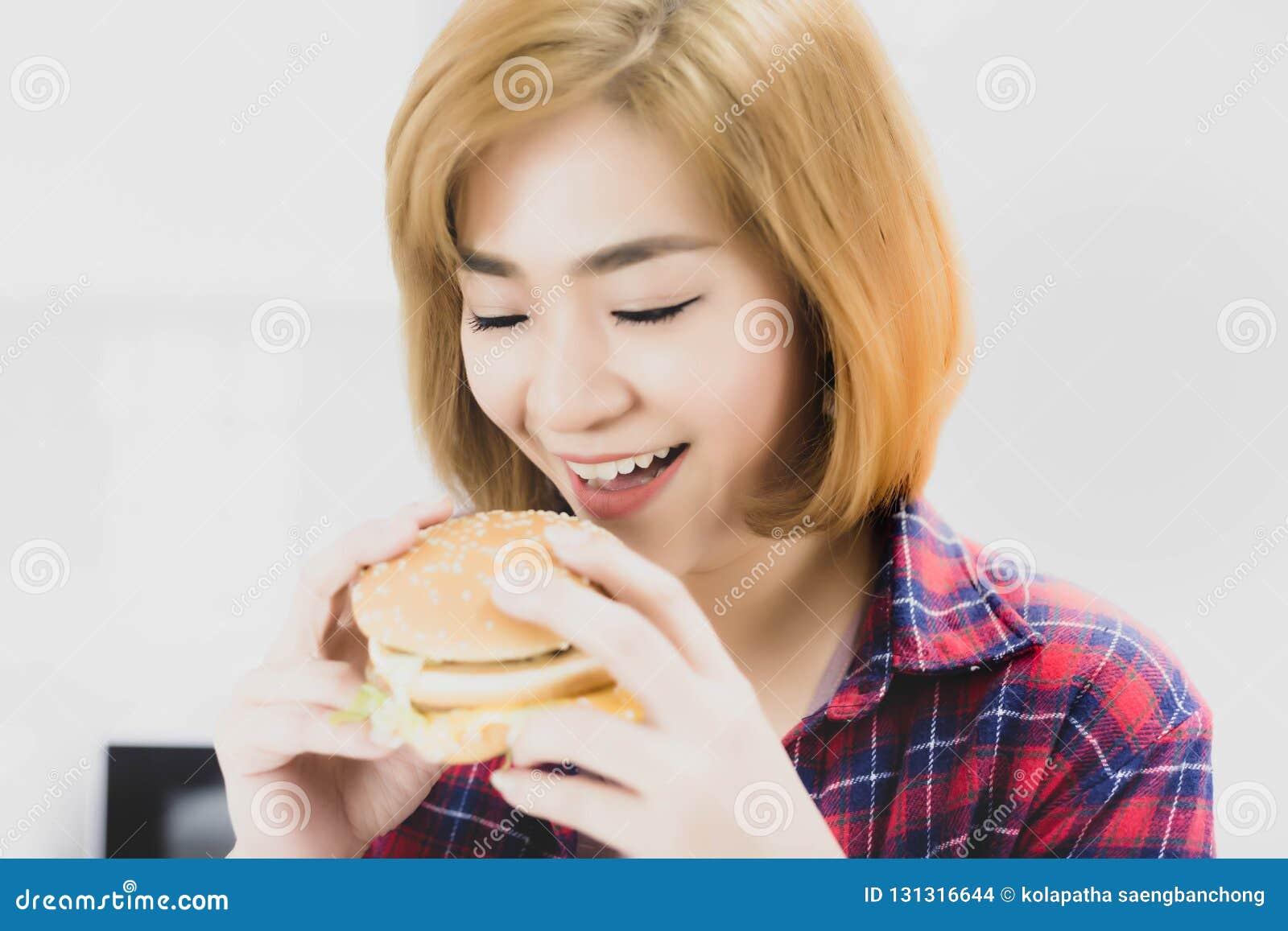 Charma härlig kvinnaförälskelse som äter hamburgaren Hamburgaren har tr
