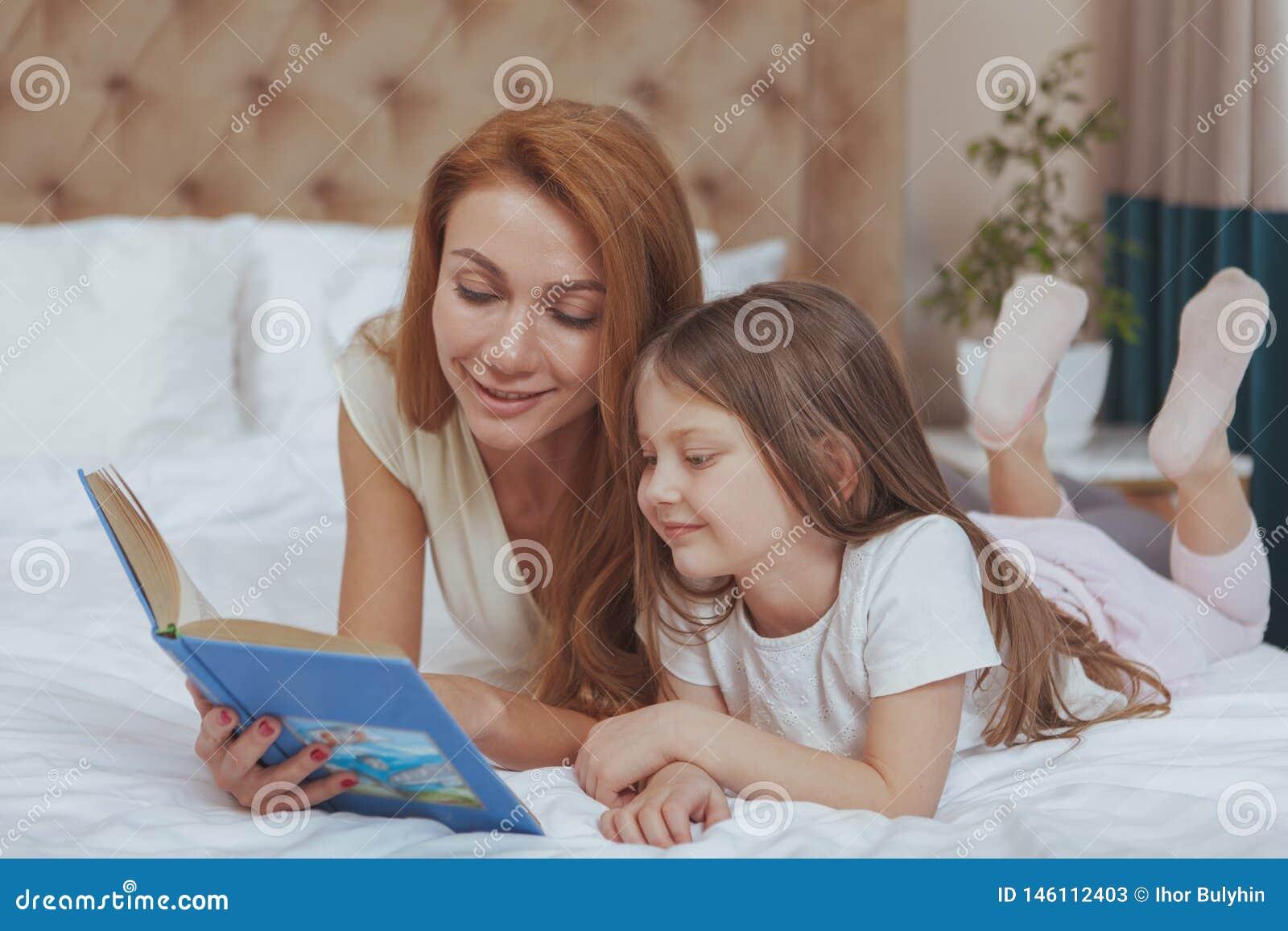 Charma kvinnan som l?ser en bok till hennes lilla dotter