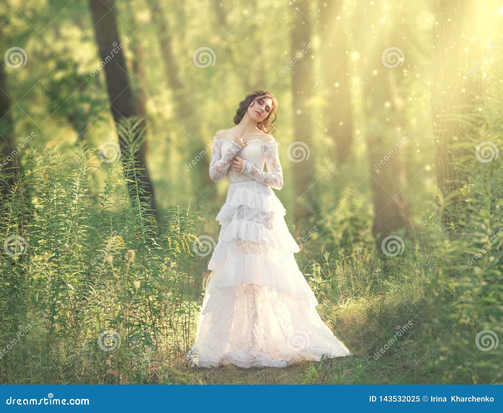 Charma skönhet med mörkt hår som in står i den ljusa skogen, gudinnan och fen av morgonsolen i varma strålar, söt flicka
