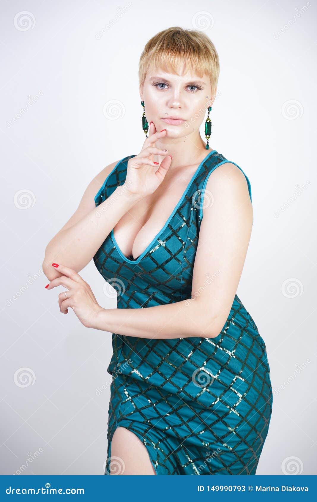 Charma som är ungt plus formatkvinna med iklätt kort blont hår en lyxig lång aftongräsplanklänning med paljetter och ställningar
