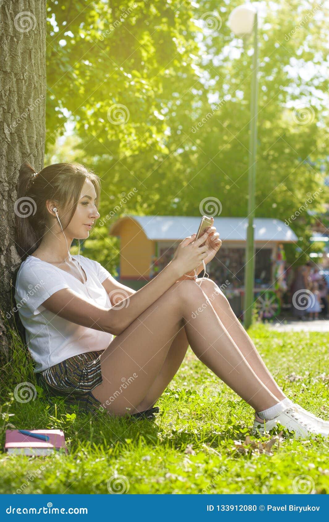 Charma studenten Girl Sitting på grönt gräs