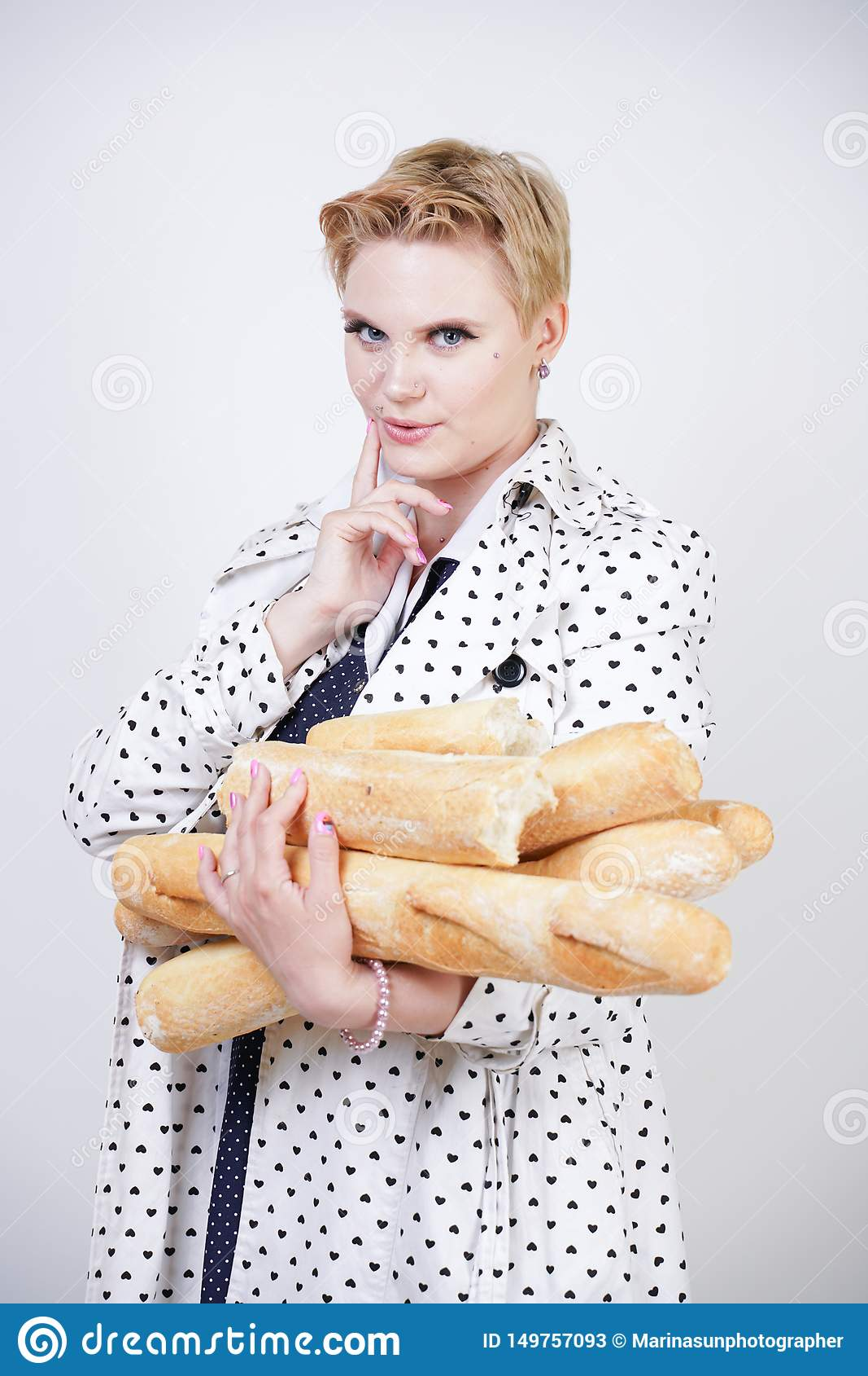 Charma utvikningsbrudkvinnan med kort hår i ett vårlag med prickar som poserar med bagetter och att tycka om dem på en vit backgr