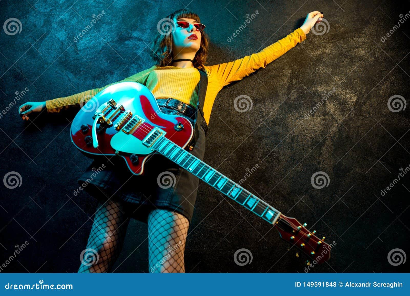 Charmante hipster vrouw met krullend haar met rode gitaar in neonlichten De musicus van de rots speelt elektrogitaar jaren  90
