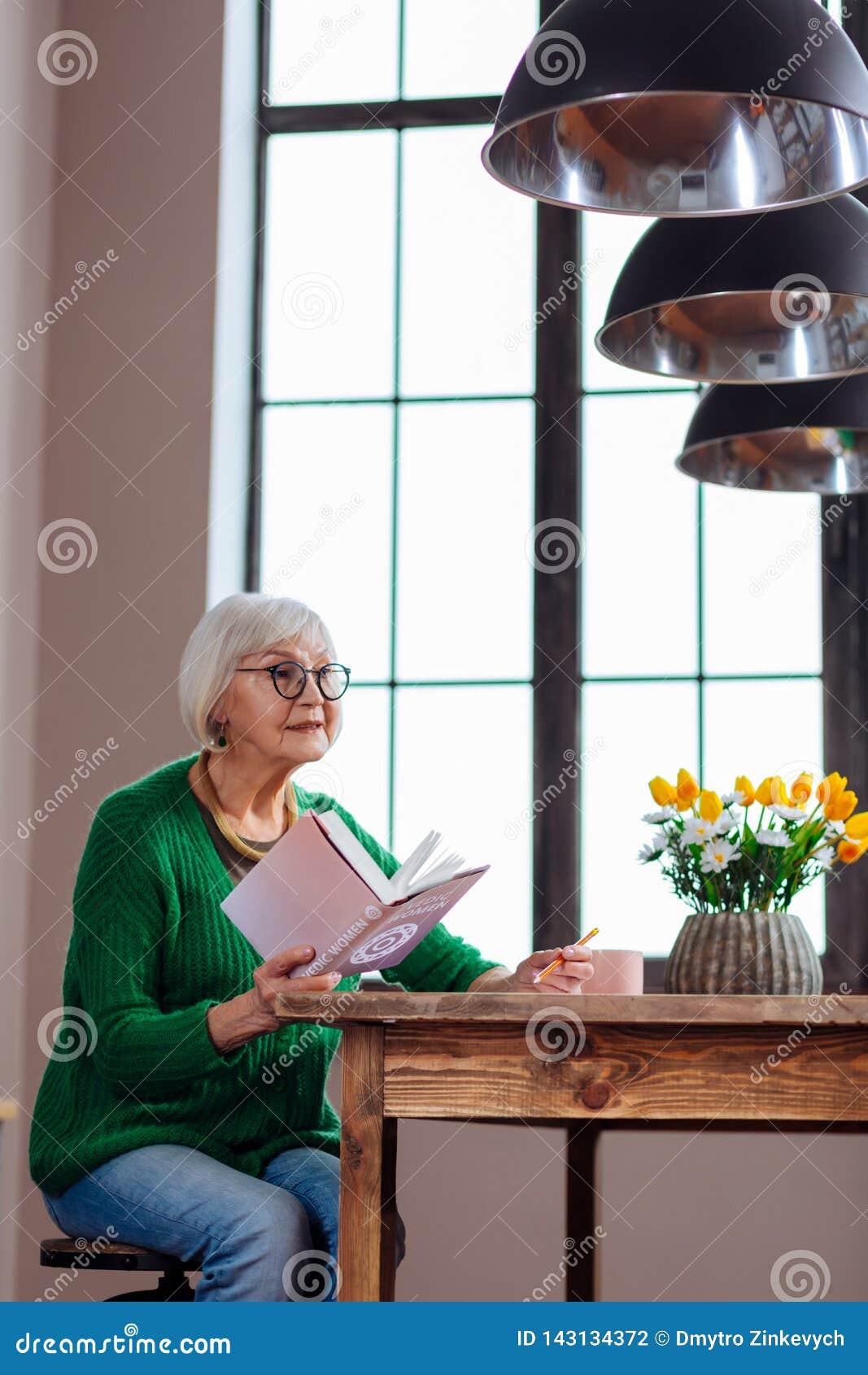 Charmante oma die aan iemand antwoorden die holdingsboek in hand roepen