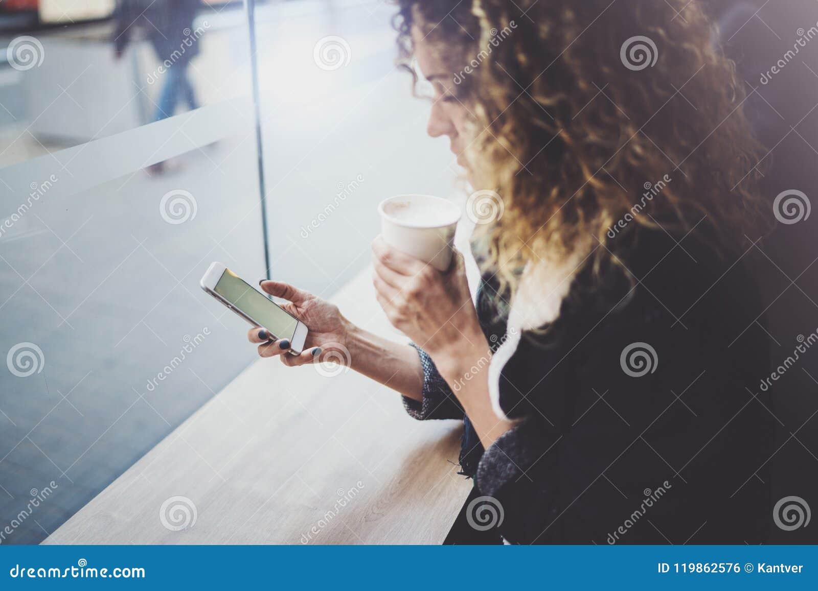 Charmante vrouw met mooie glimlach die mobiele telefoon met behulp van tijdens rust in koffiewinkel Vage achtergrond