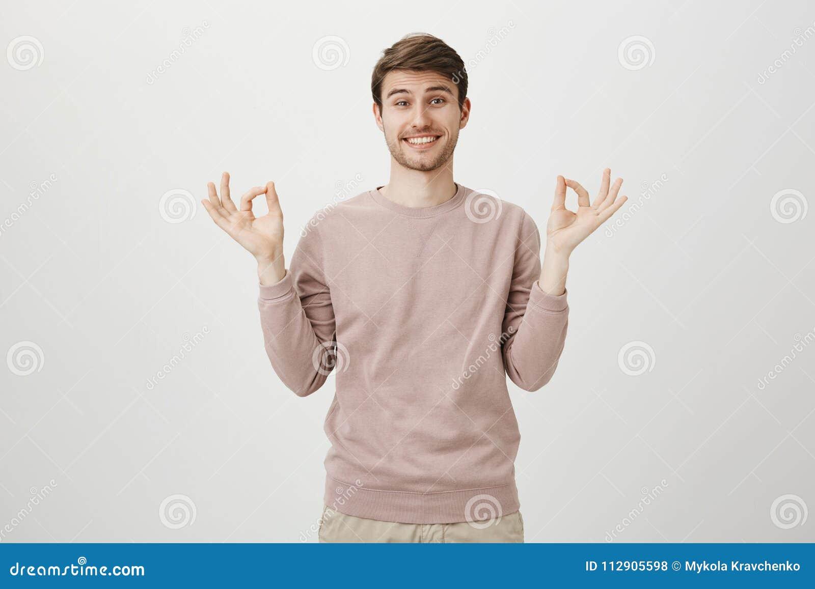 Charmerend de jonge mens met heldere glimlach en varkenshaar, die toevallige o.k. trui en tonen of zen gebaar dragen terwijl stat