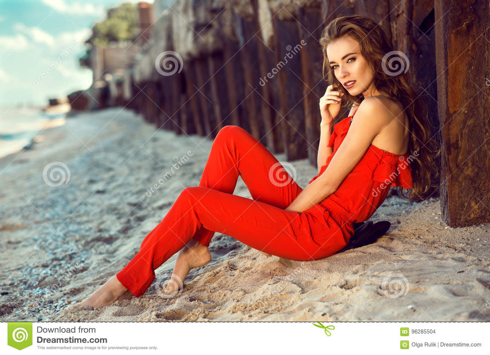 Charmerend elegante jonge vrouw in koraal rode schouder jumpsuit zitting op het strand bij de oude roestige stapels