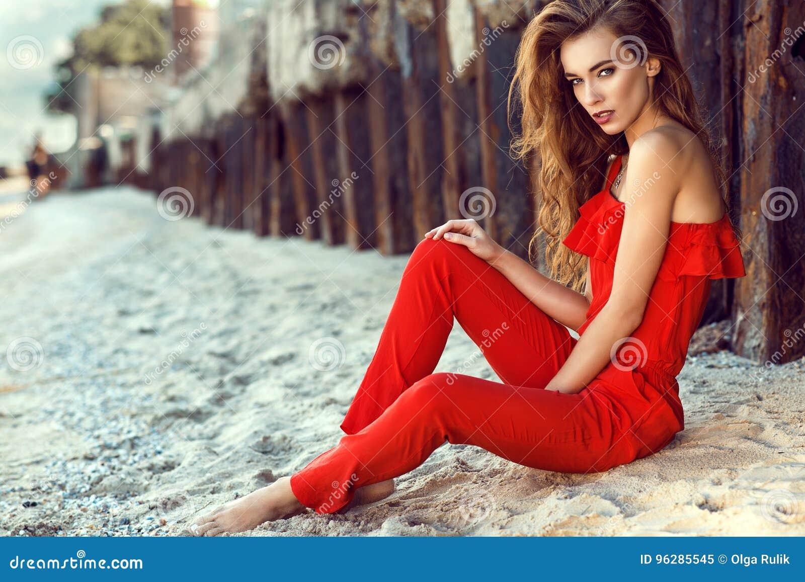 Charmerend jonge vrouw met lang haar in koraal rode schouder jumpsuit zitting op het strand bij de oude roestige stapels