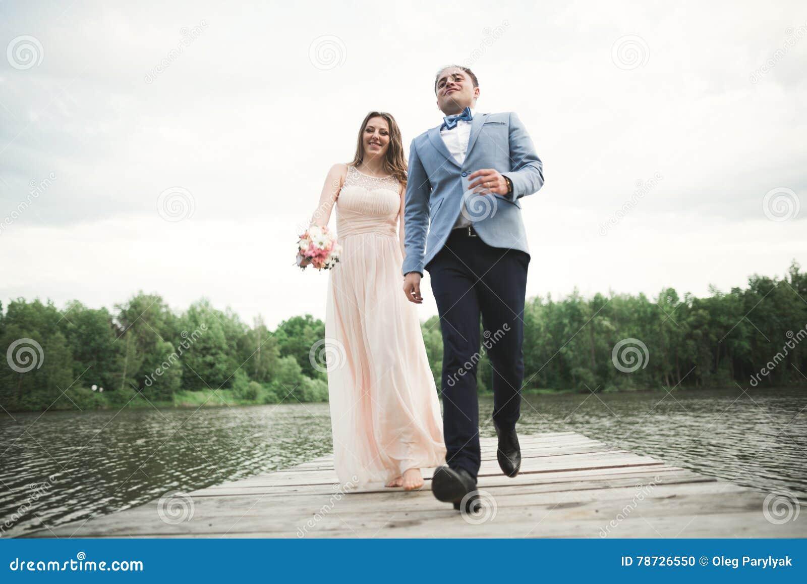 Charmig brud, elegant brudgum på landskap av berg och solnedgång på sjön ursnyggt bröllop för par