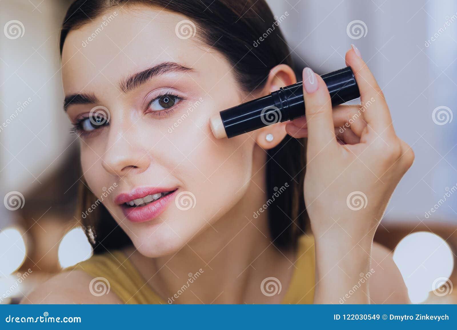Charmig kvinna som använder täckstiftpinnen, medan sätta på makeup