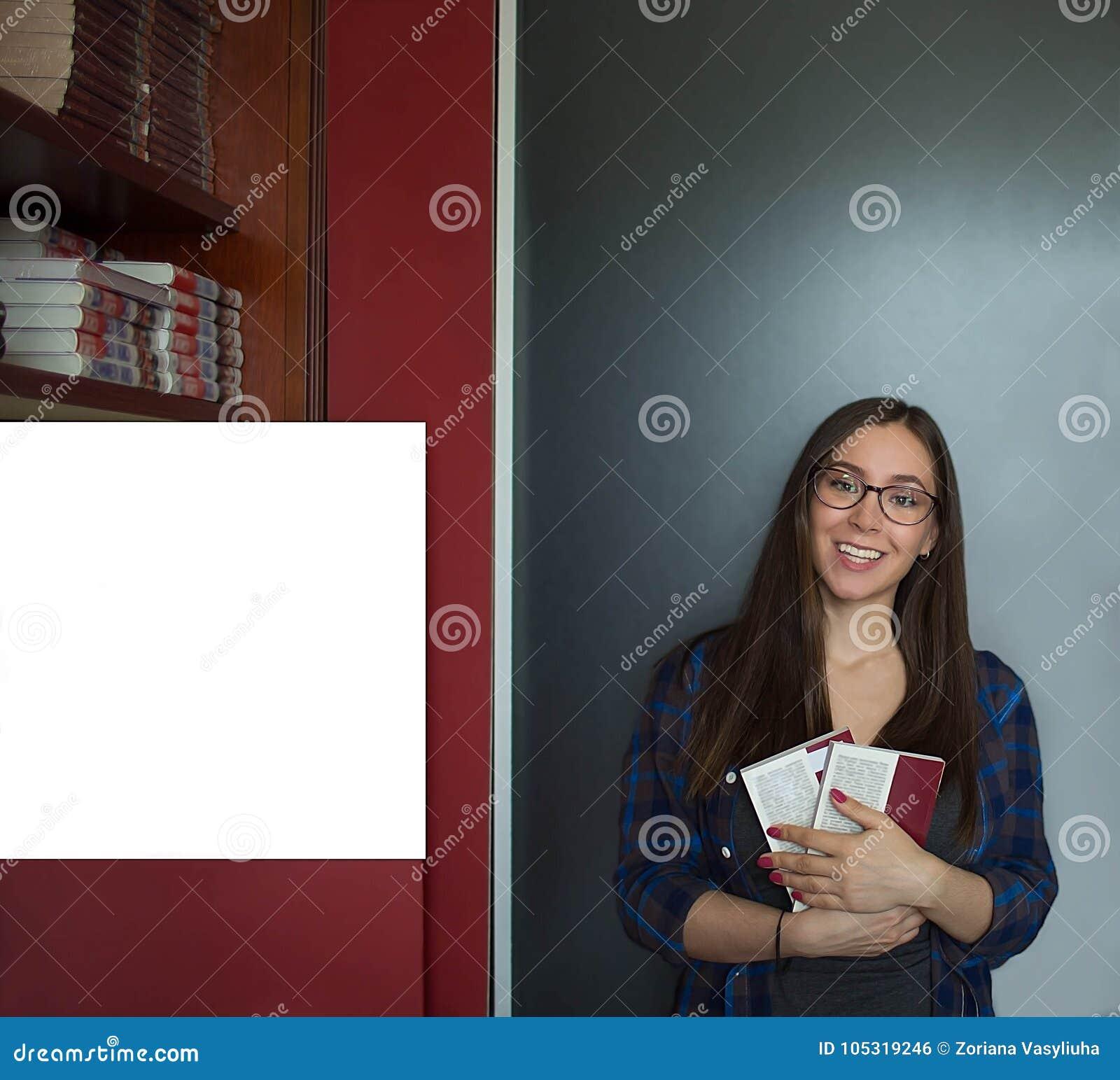 Charmig kvinnlig med litteratur som poserar för kamera under att lära i universitet