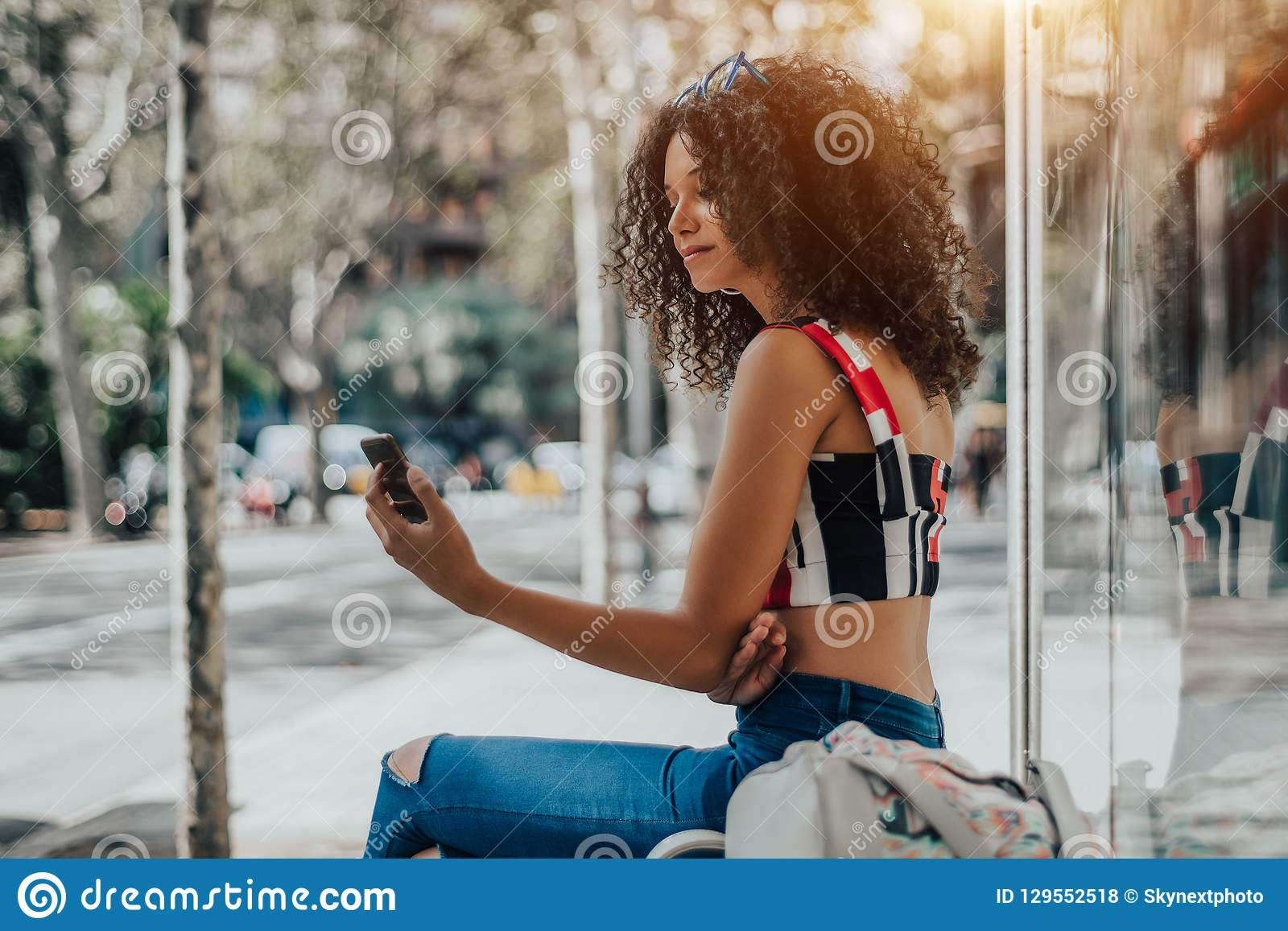 Curly Girl With Cellphone On The Bus Stop Stock Photo