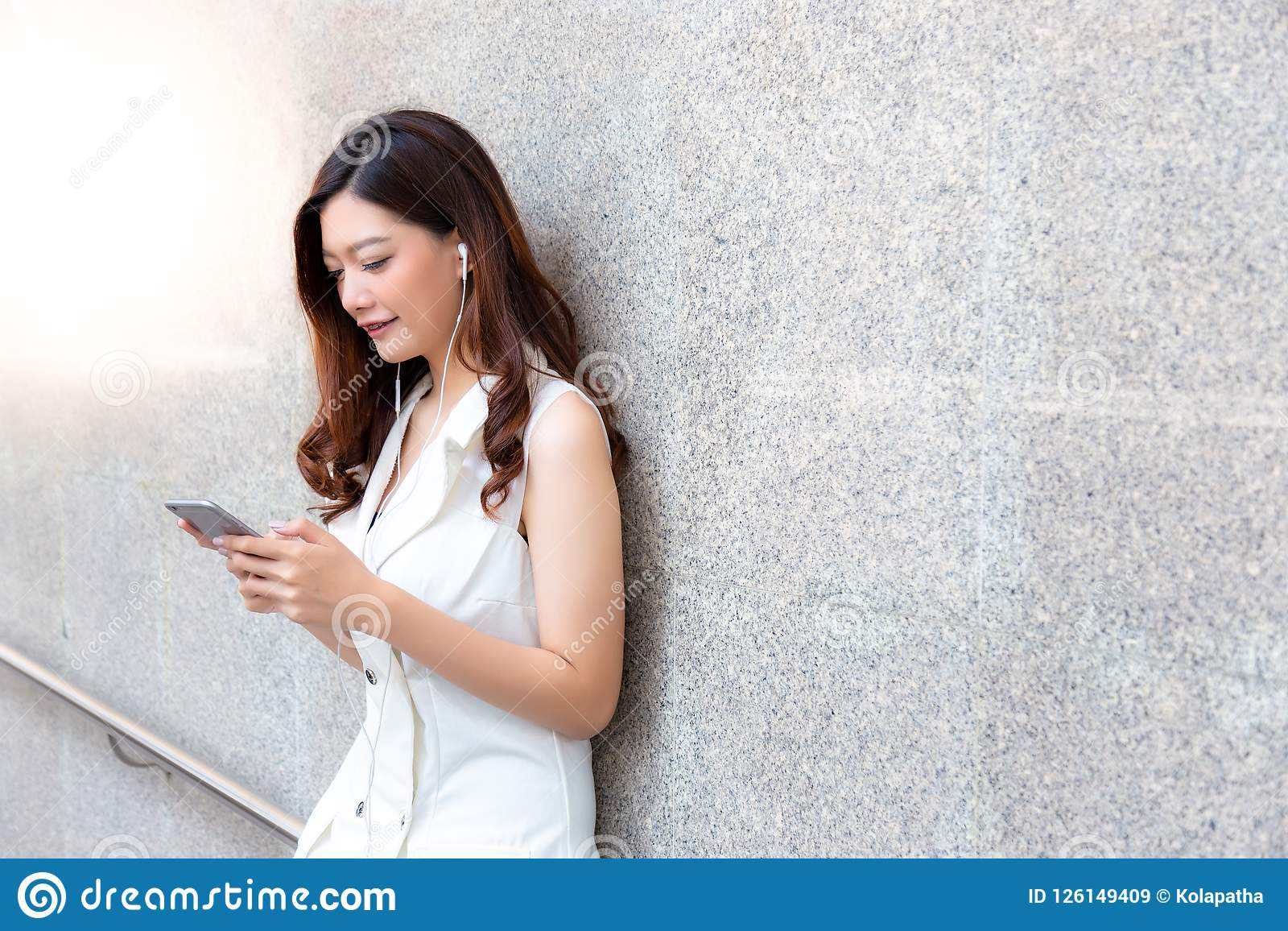 Charming beautiful asian woman. Attractive beautiful girl is listening nice music by using smartphone, earphone at her office