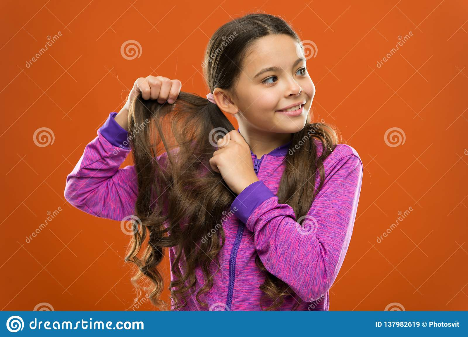 Charming beauty. Girl active kid with long gorgeous hair. Strong and healthy hair concept. How to treat curly hair. Easy