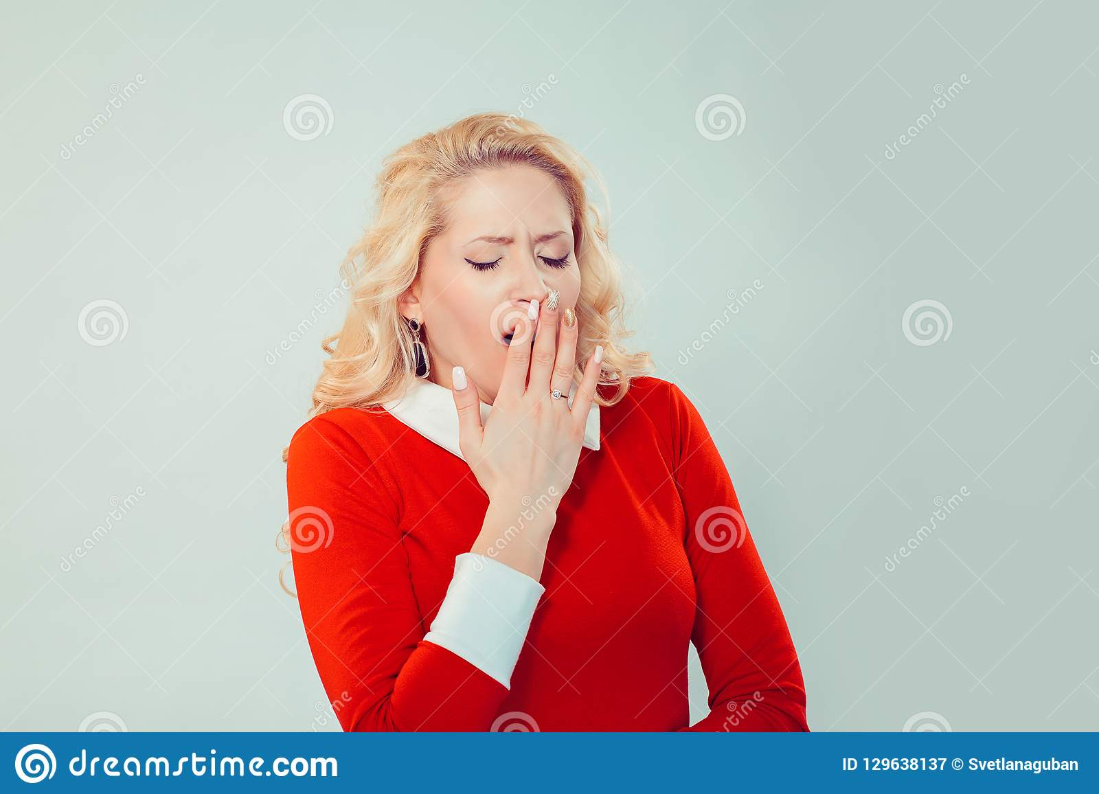 Sleepy woman covering mouth while yawning