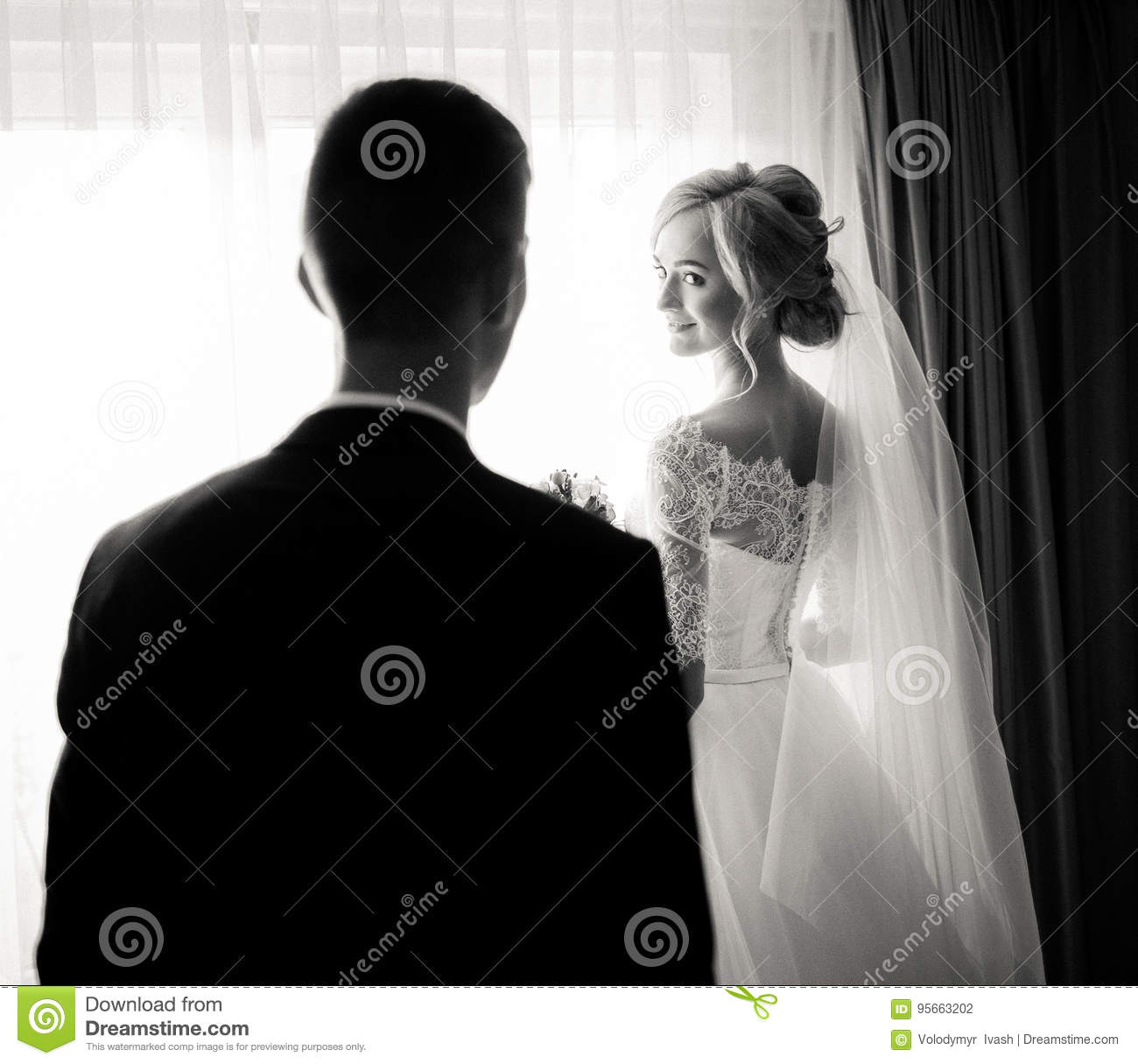 Charming blonde bride looks over her shoulder at groom