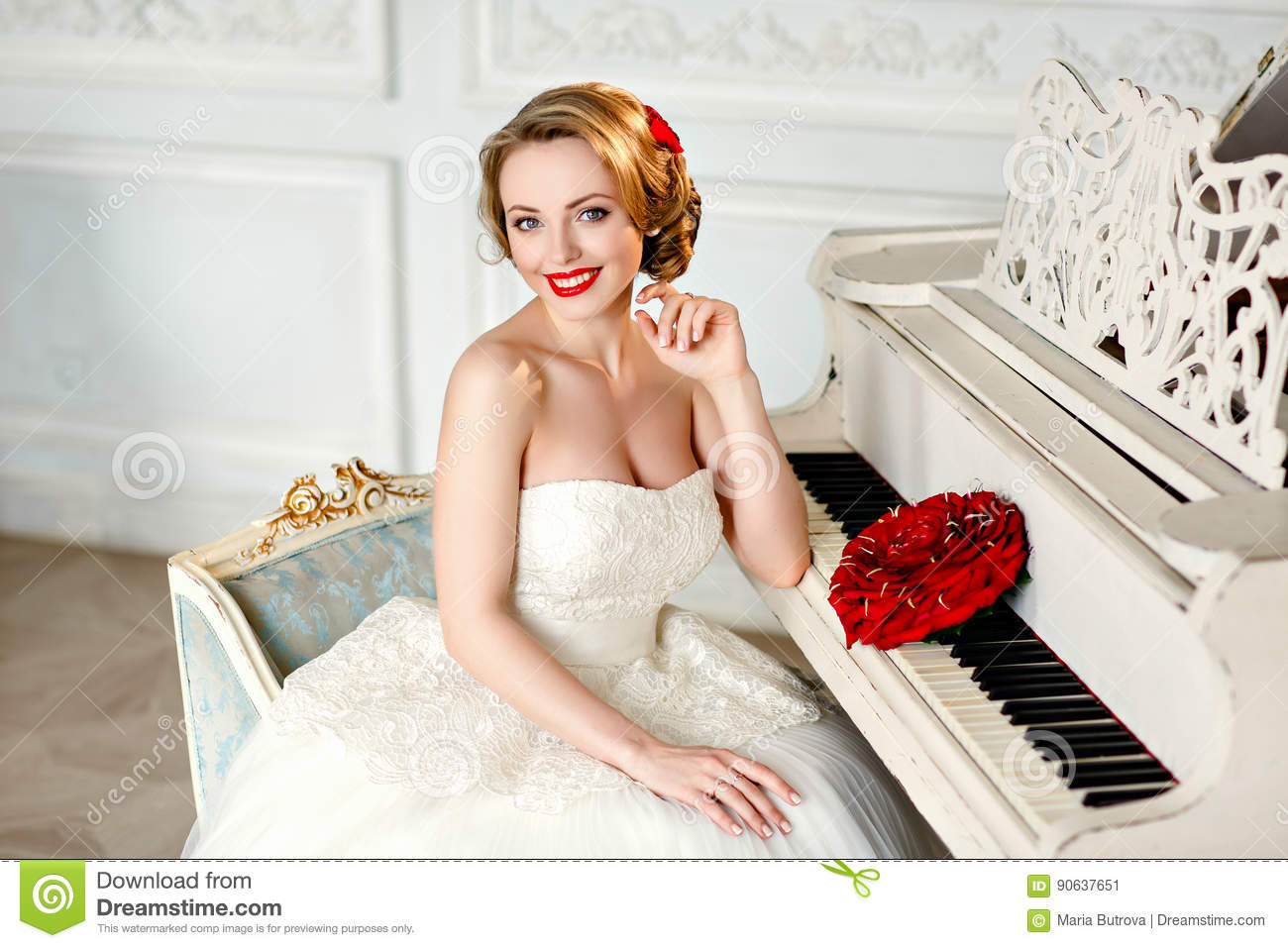 70759c469b5 Charming blonde girl with beautiful smile in a white lace dress and a  bouquet of red roses sits in an old chair next to the piano on the  background of the ...