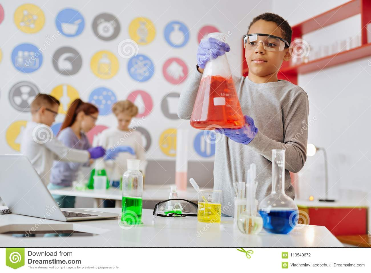 Charming Boy Observing Chemical Reaction In The Flask Stock
