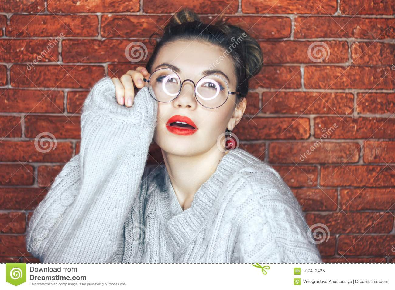c3486bc4f5 Charming brunette young woman in glasses wearing gray sweater touching  glasses with eyes closed posing. Red brick background. Red lips.