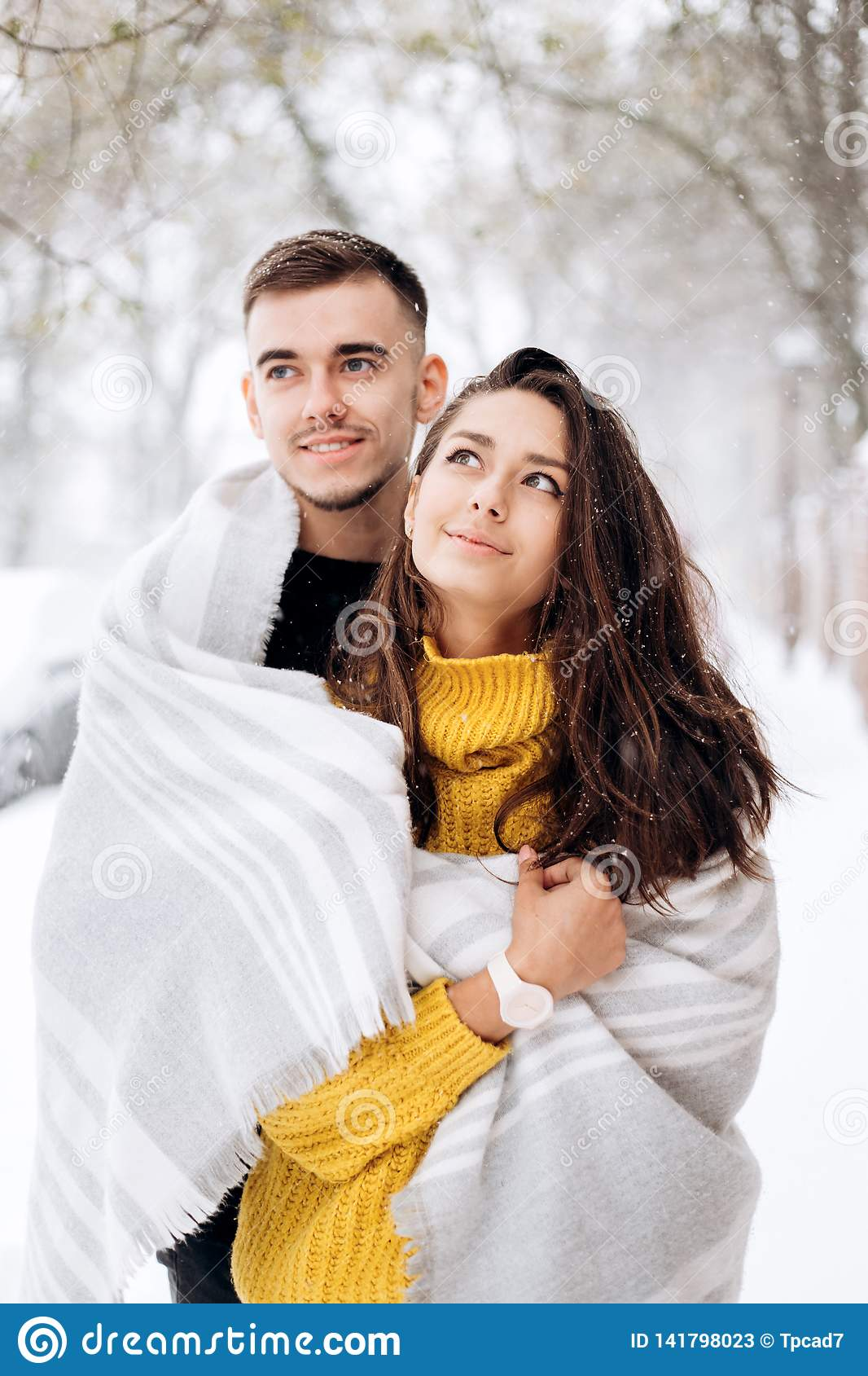 Charming dark-haired girl dressed in a yellow sweater and her boyfriend wrapped together in a gray scarf are standing in