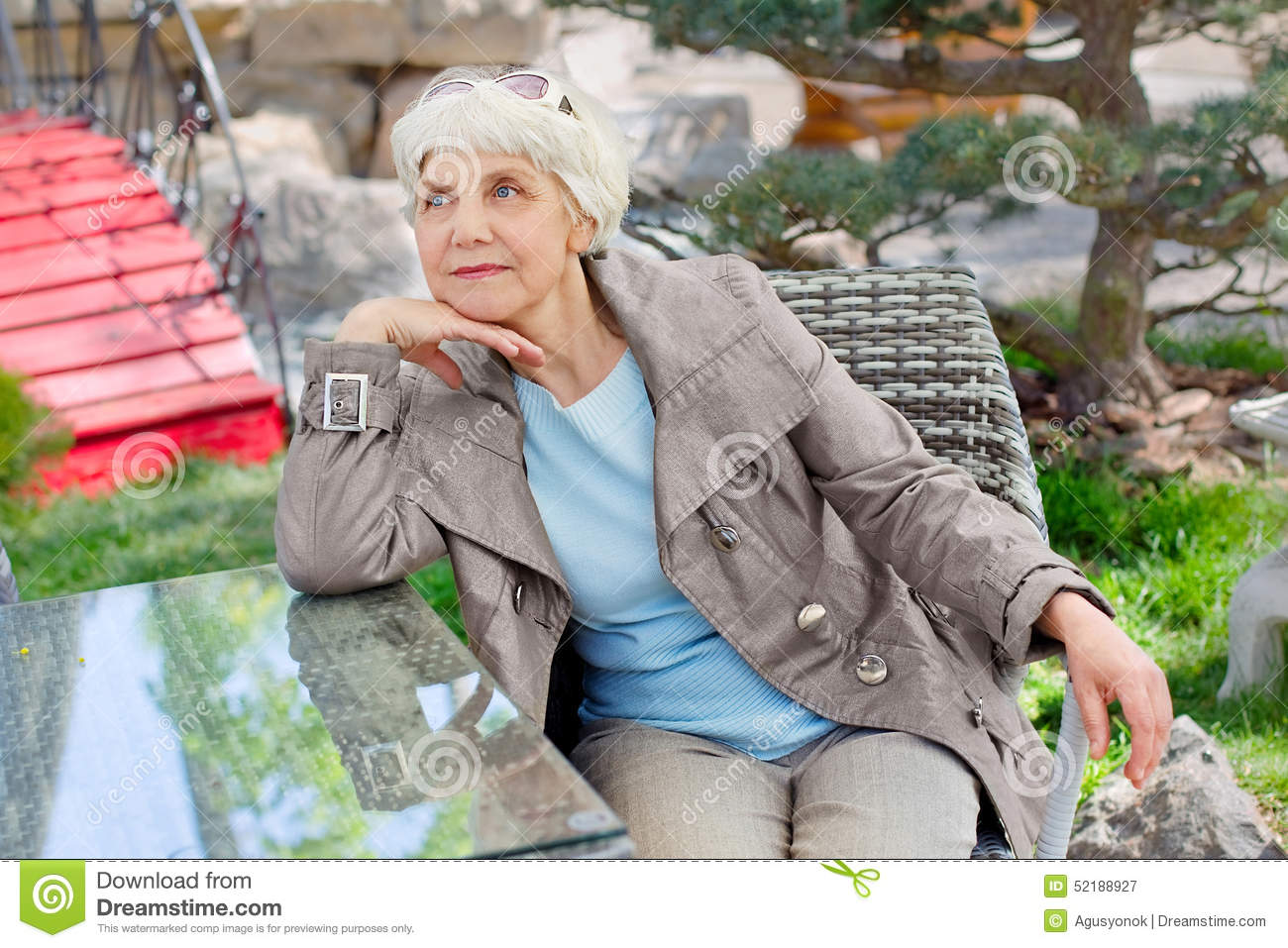 Charming elderly gray-haired woman relaxing sitting in the garden