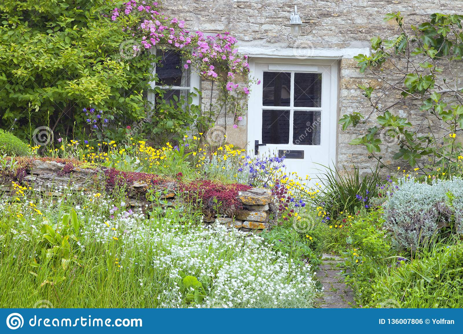 Charming english cottage with white doors flowers in the garden