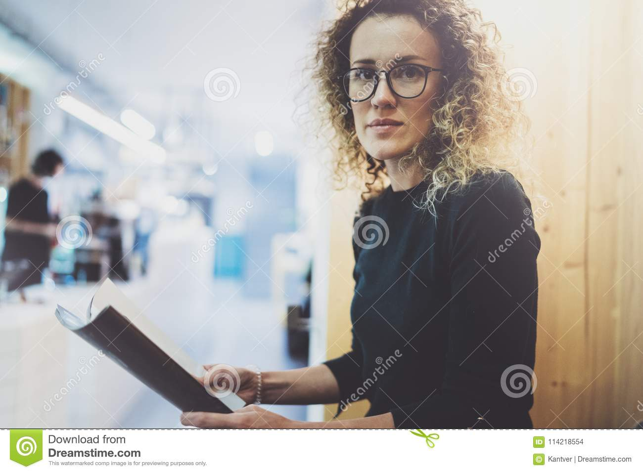 6962553c1b Charming fashionable woman with eyes glasses reading magazine sitting  indoor in urban cafe.Casual portrait
