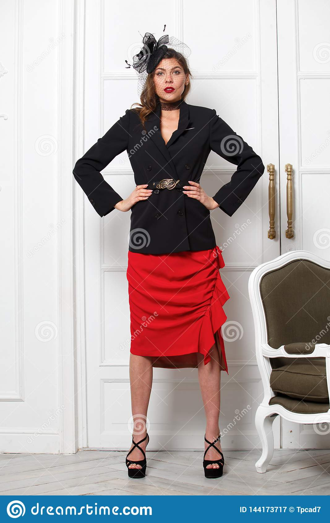 Charming girl dressed in a stylish black jacket, red skirt and a little fashionable hat poses against a white wall in