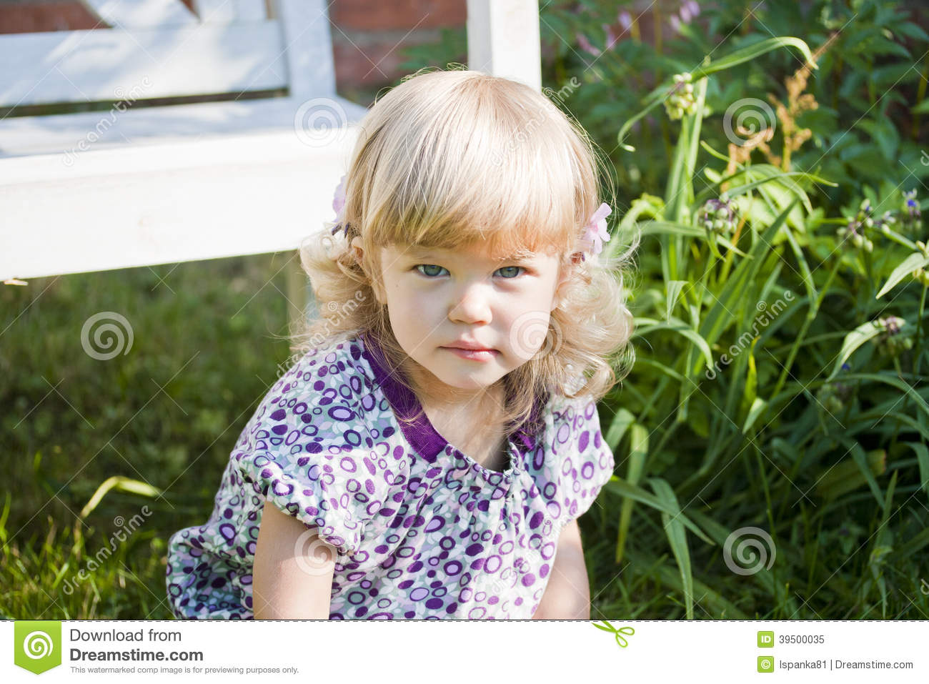 The charming girl in a garden in an elegant dress