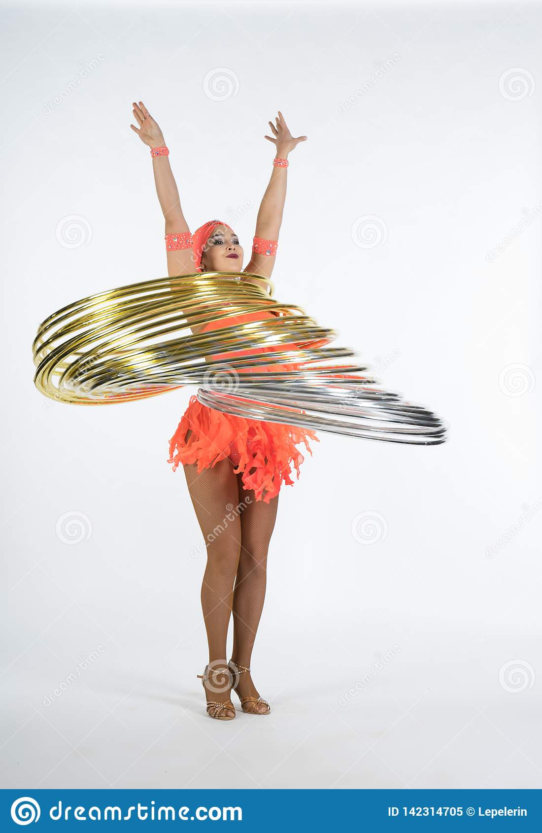 A charming girl performs circus elements with a hula Hoop
