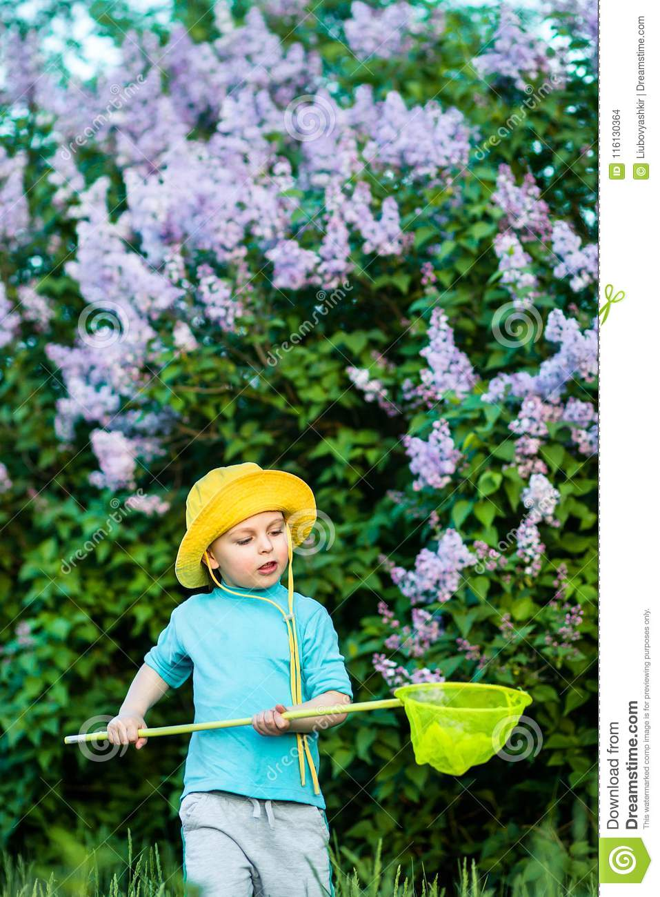 A charming kid playing with a scoop on a meadow in a warm and sunny summer or spring day.