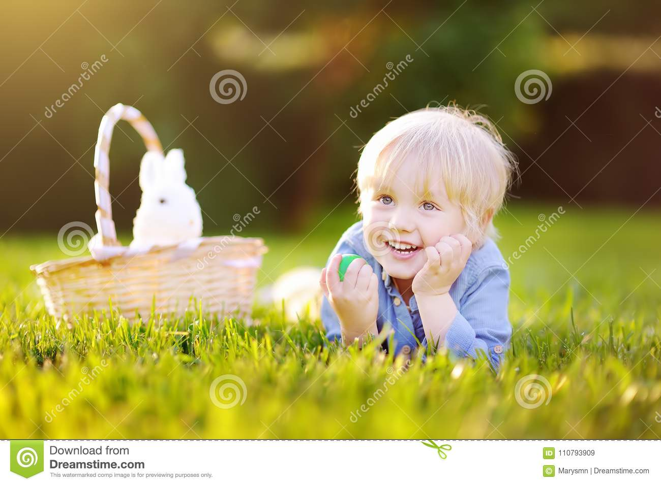 Charming little boy hunting for easter egg in spring park on Easter day