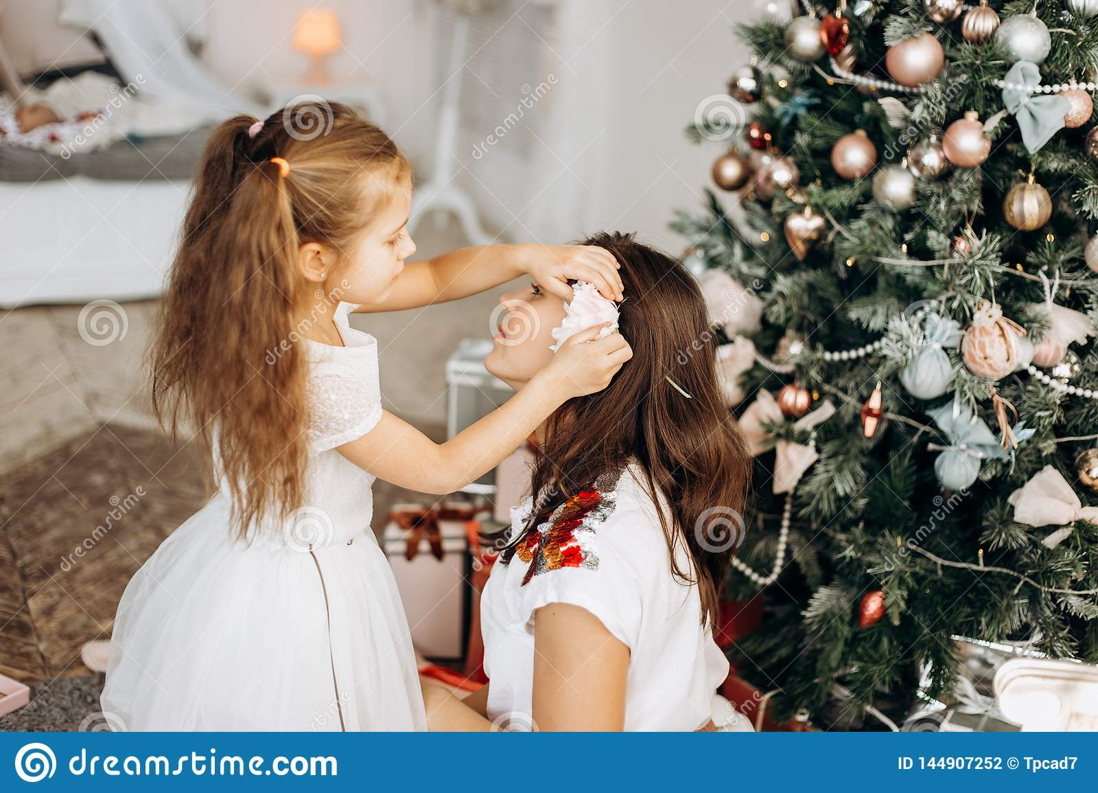 Charming little daughter in nice dress put a flower in mothers hair near the New Year`s tree