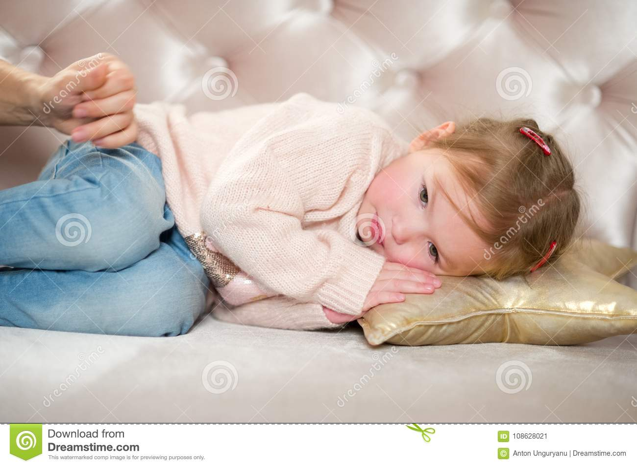 Charming Little Girl Falls Asleep On A Pink Sofa. The Mother`s Hand  Caresses The Baby.
