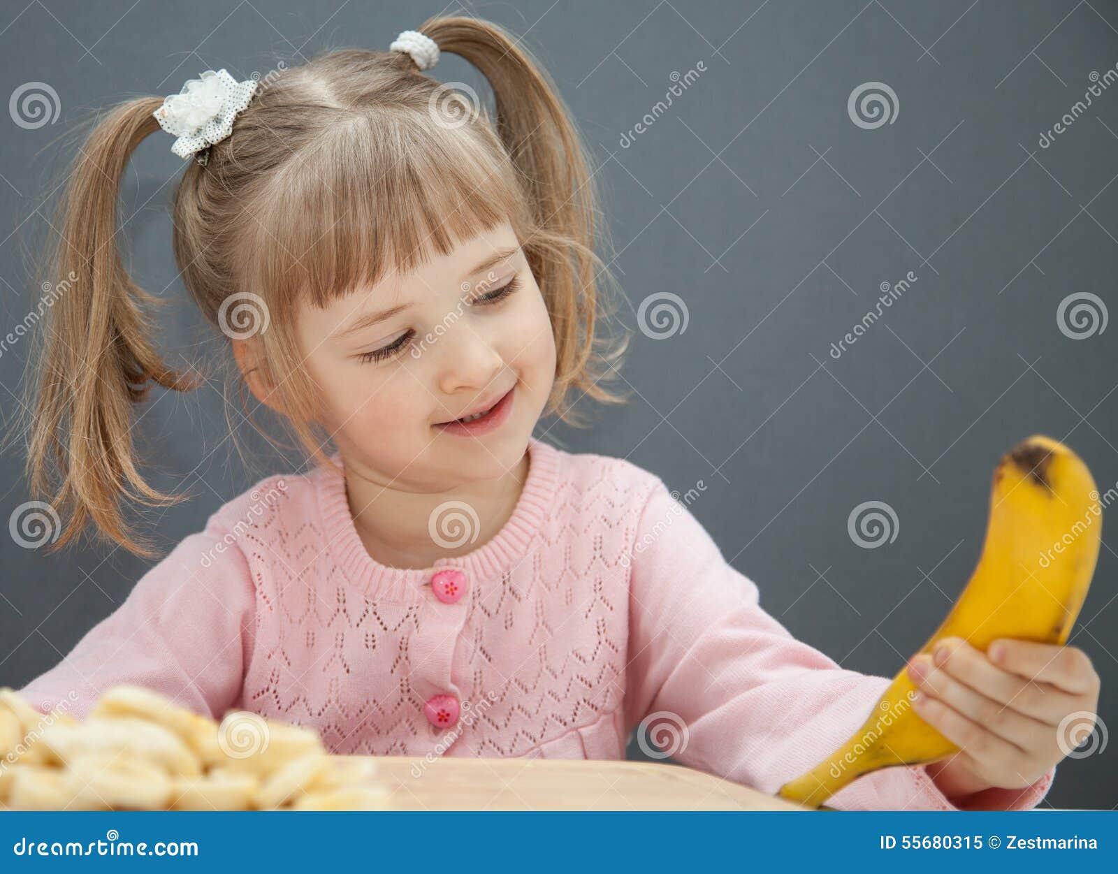 Charming little girl holding a ripe banana