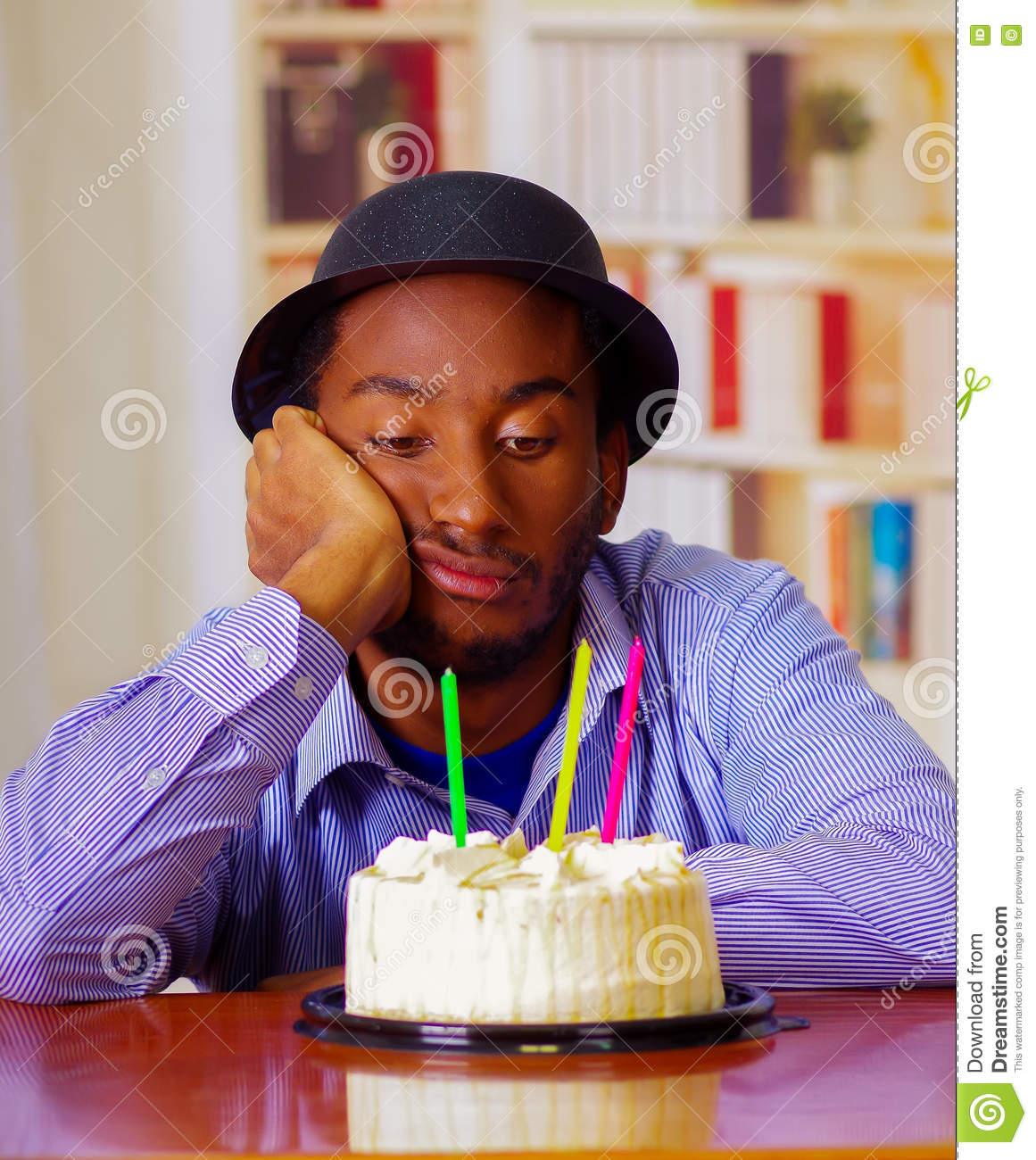 Charming Man Wearing Blue Shirt And Hat Sitting By Table With Birthday Cake In Front