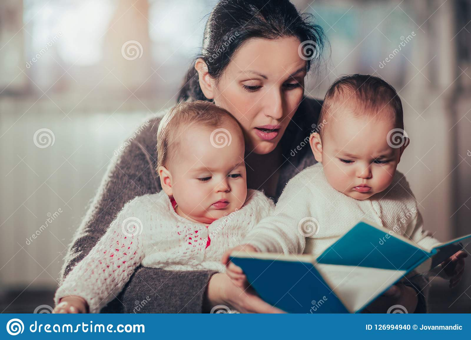 Charming mother showing images in a book to her cute twin babies