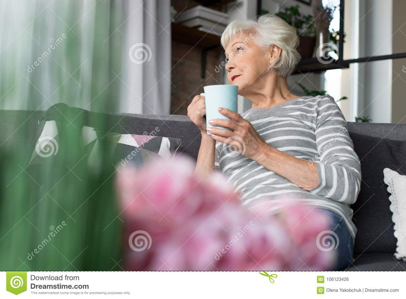 charming old woman relaxing on couch with hot drink stock photo