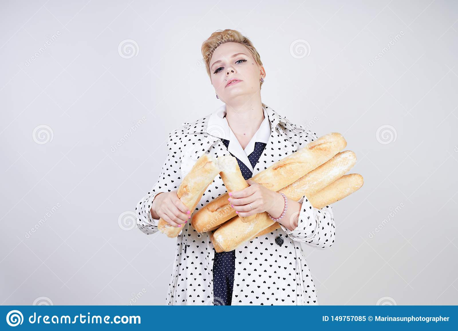 Charming pinup woman with short hair in a spring coat with polka dots posing with baguettes and enjoying them on a white backgroun