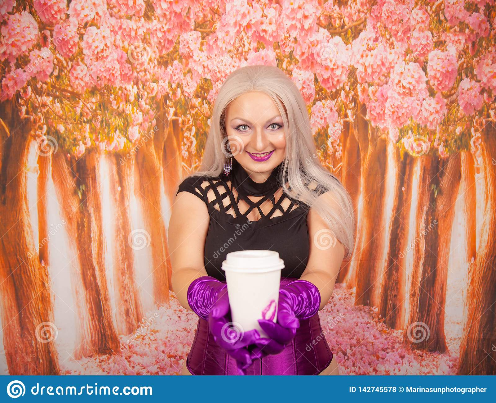 Charming plump blonde woman in a purple corset with long gloves holds a paper Cup of takeaway coffee with a mark of her lipstick k
