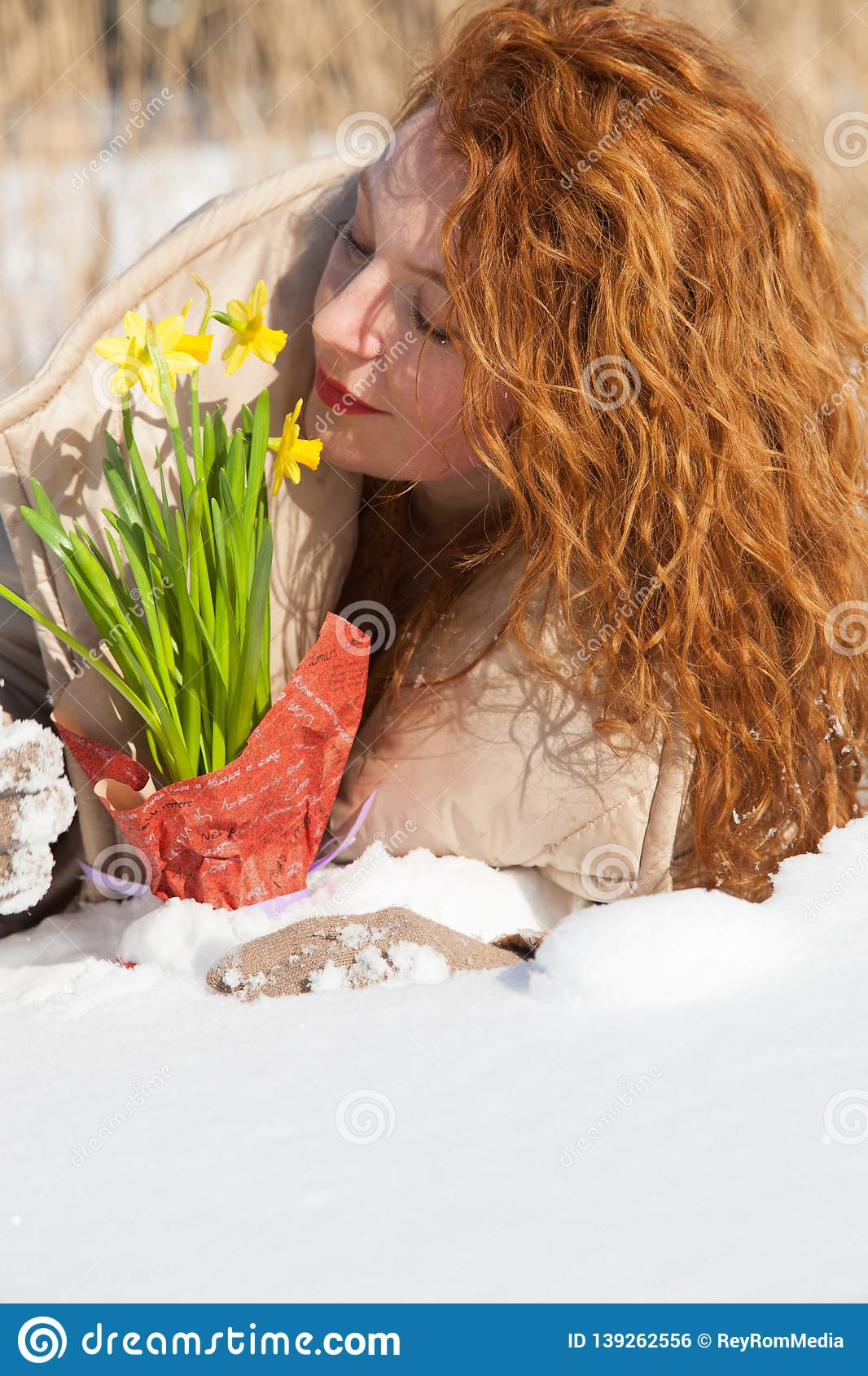 Charming red haired woman smelling yellow snowdrops while resting in snow