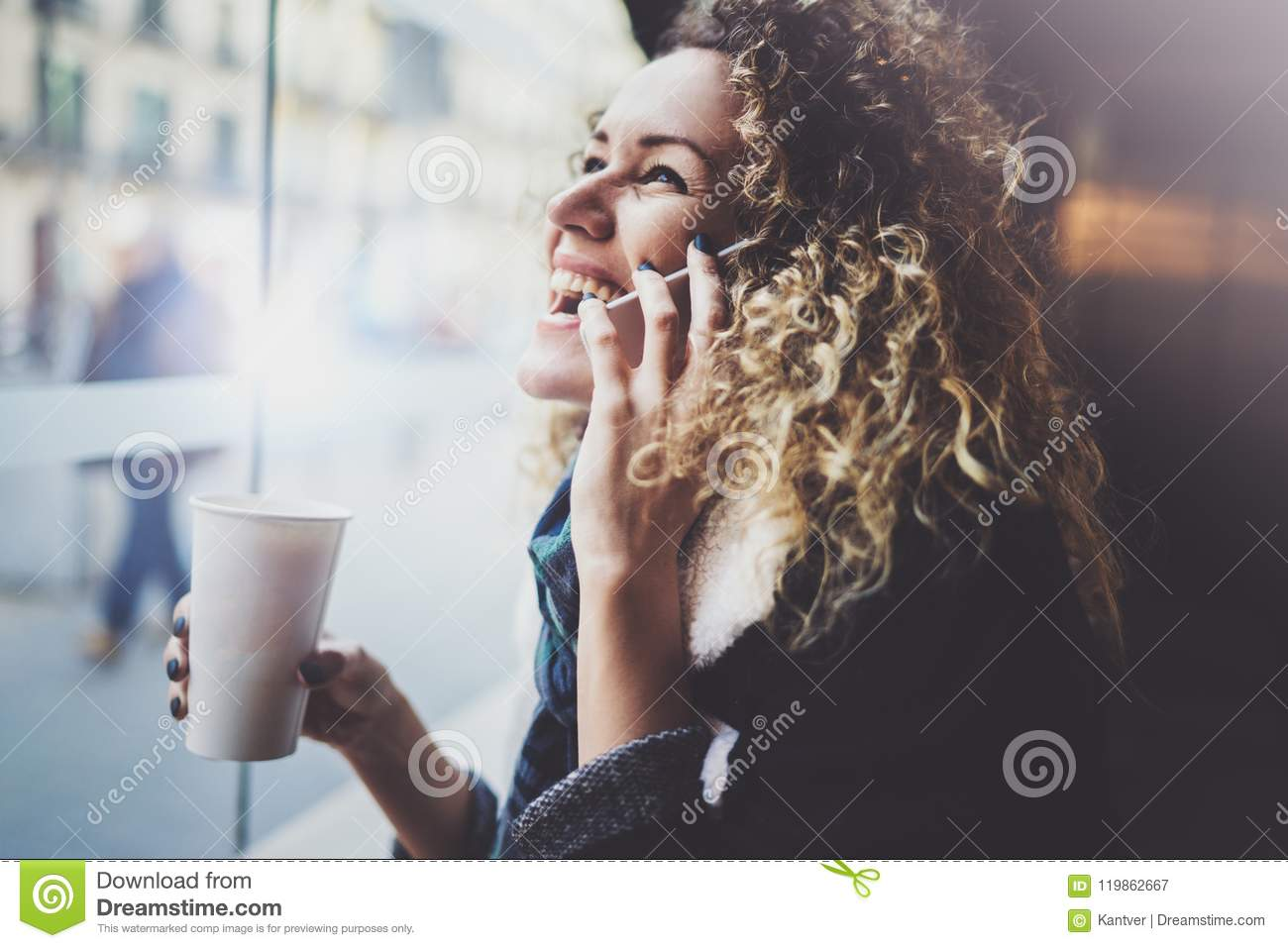 Charming woman with beautiful smile using mobile phone during rest in coffee shop. Blurred background.