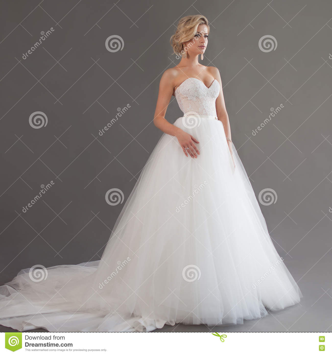 Charming young bride in luxurious wedding dress. Pretty girl in white. Emotions of happiness, gray background