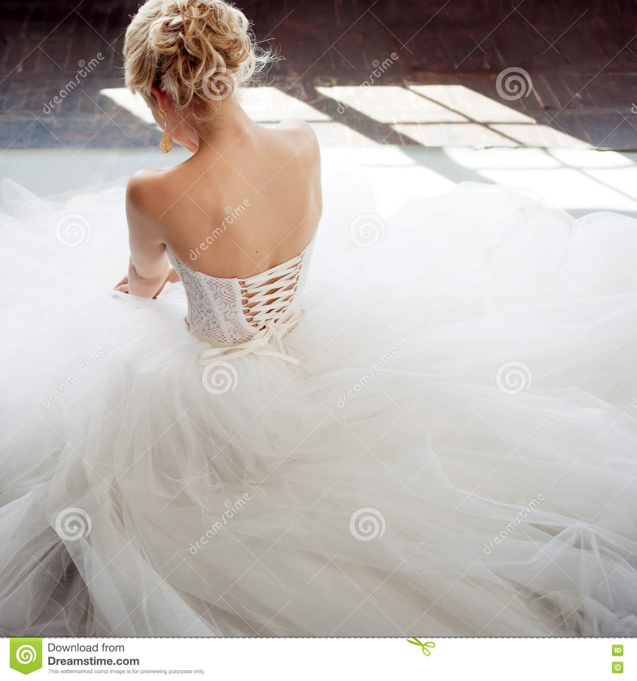 Charming young bride in luxurious wedding dress. Pretty girl in white. Gray background. Back