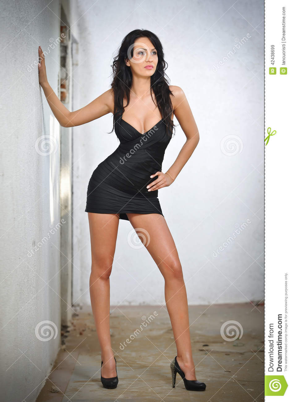 f0c0cbe2c9d36 Charming young brunette woman in black tight fit dress posing against a wall