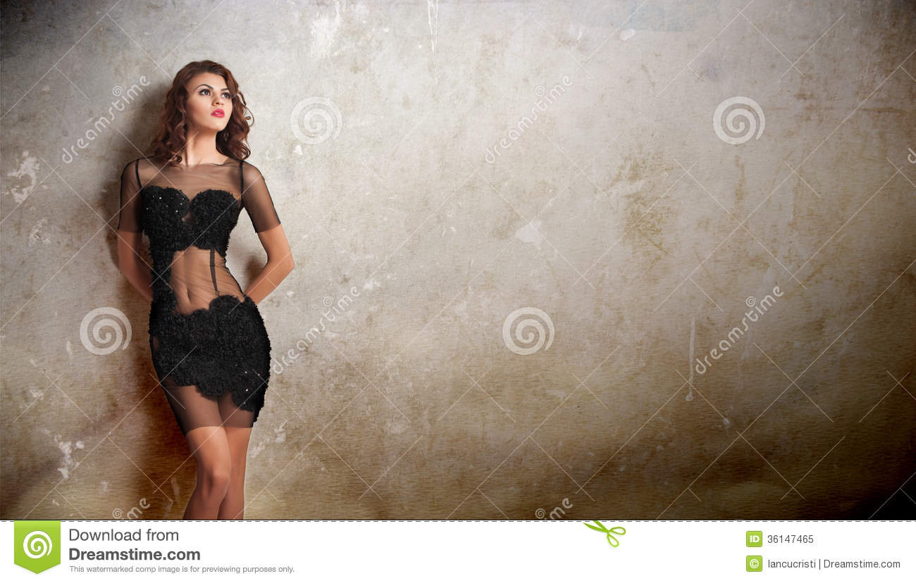 Charming young brunette woman in transparent lace black dress leaning against an old wall. gorgeous young woman near old wall