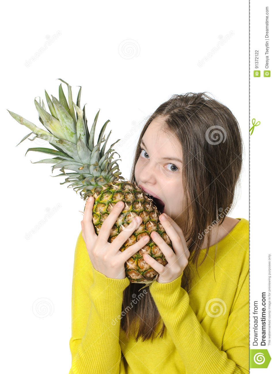 Charming young girl bites a large ripe pineapple.