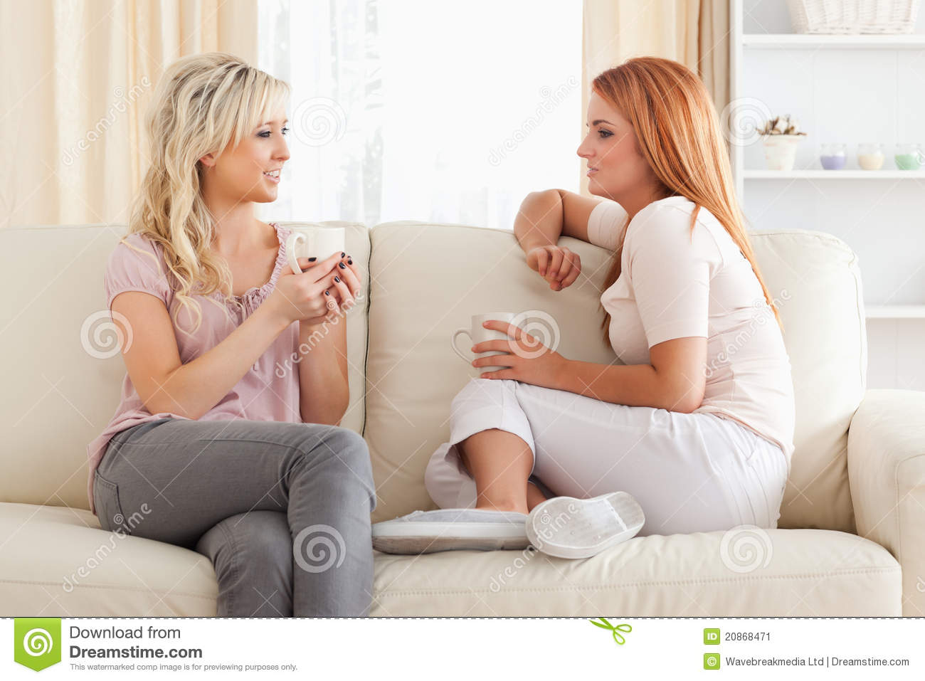 Charming young Women sitting on a sofa with cups
