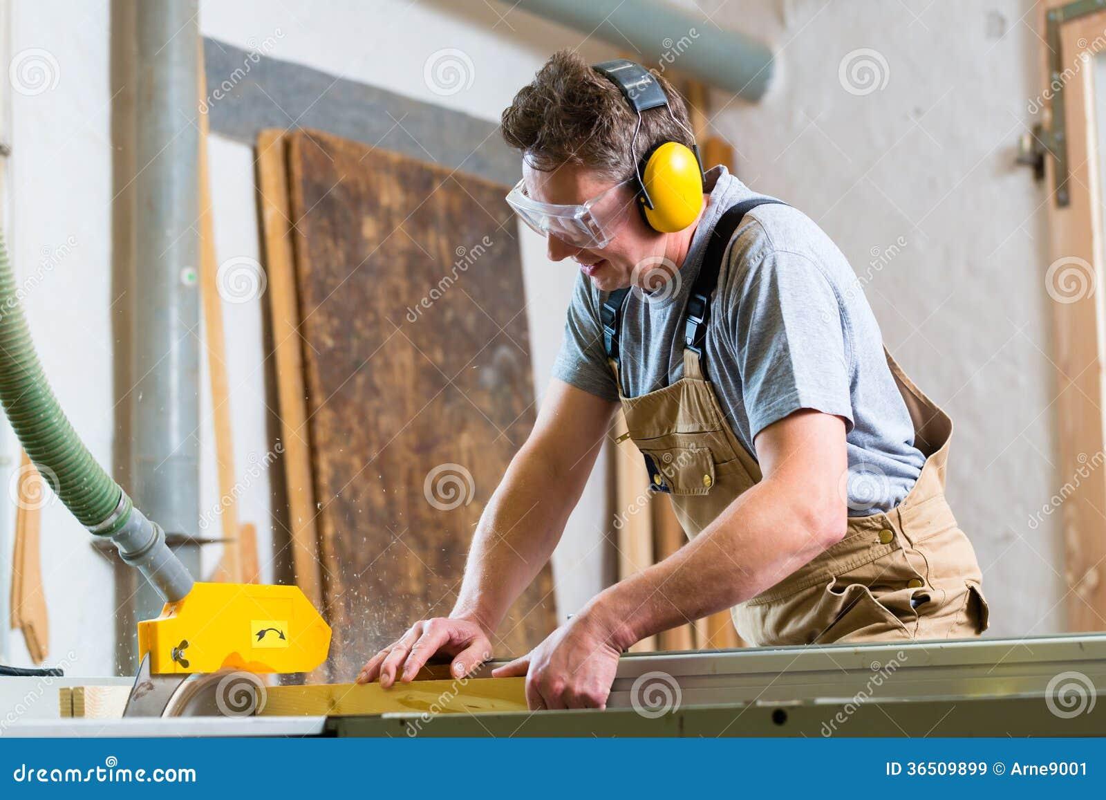 Charpentier à l aide de la scie électrique en menuiserie